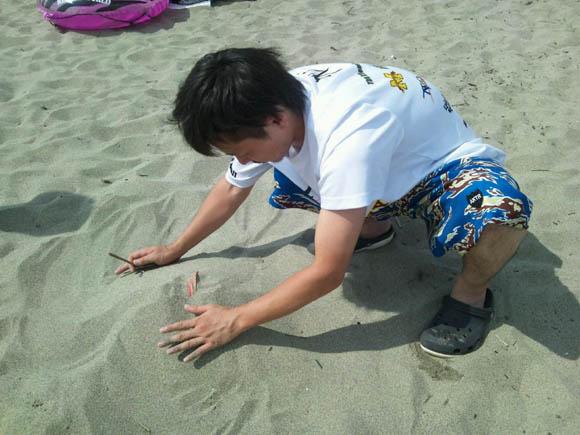 サンダルを埋めるOTKさん