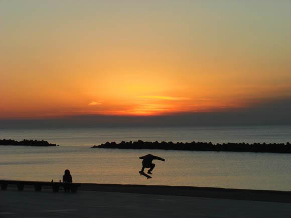 沈む夕日とスケートボーダー